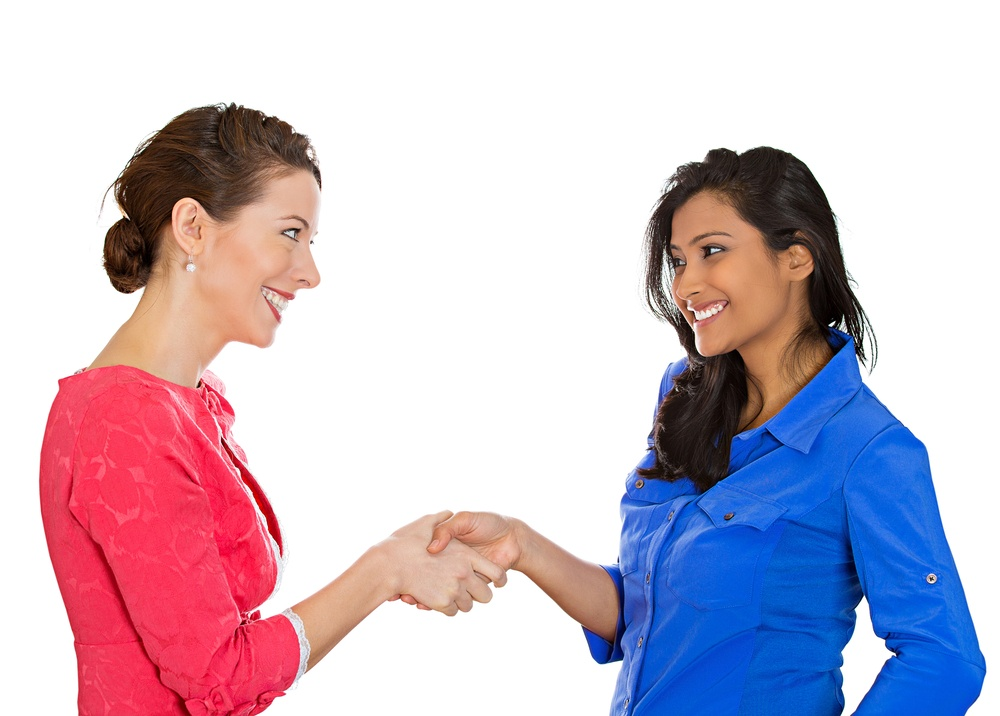 Two happy business women shaking hands, after conflict resolution, finding solution to problem, isolated white background. Positive human emotions, facial expressions, attitude